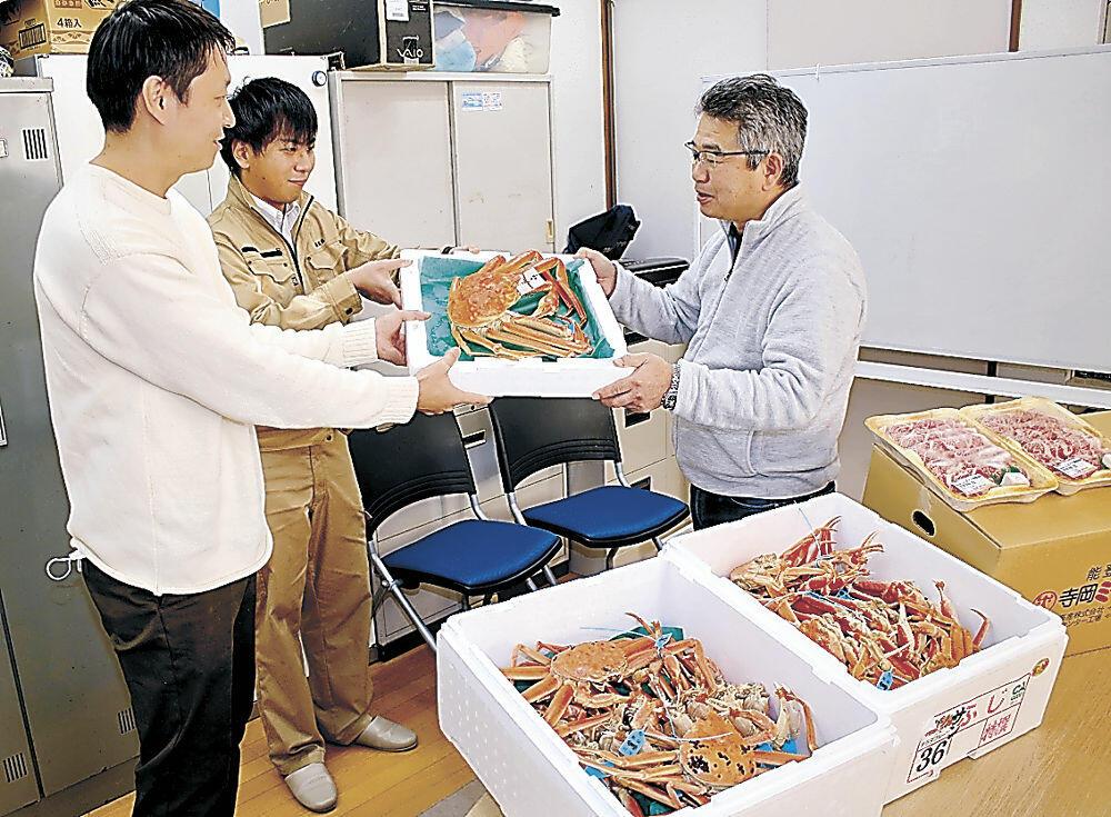 萩山さん(右)に加能ガニを贈る志倉社長(左)=宝達志水町菅原の「しお子どもの家」