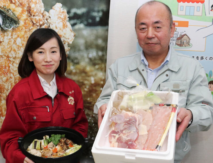 鍋のセットを手にする柳沢さん(右)