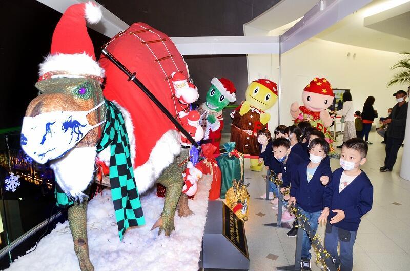 サンタクロースの衣装などを身に着けたフクイサウルスの模型を眺める園児ら=11月27日、福井県勝山市の県立恐竜博物館
