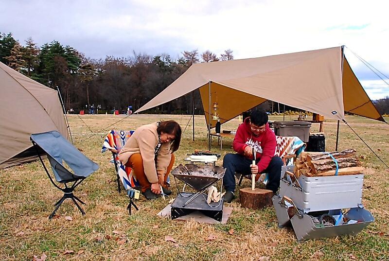大芝生広場にテントやタープを設営し、たき火の準備をする参加者