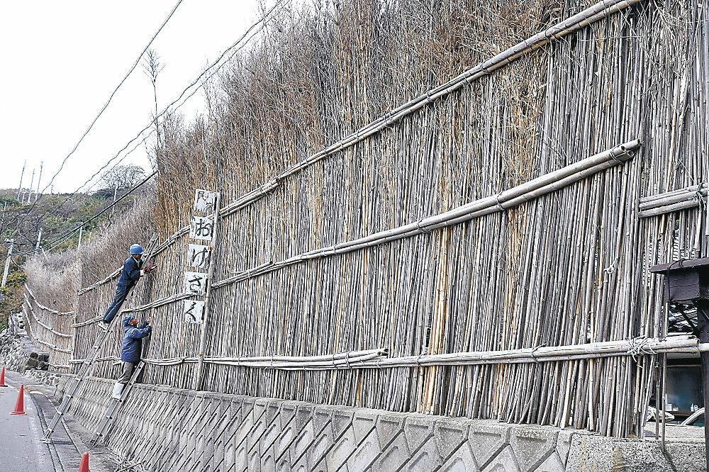 間垣の補修作業を進める地元住民=輪島市大沢町