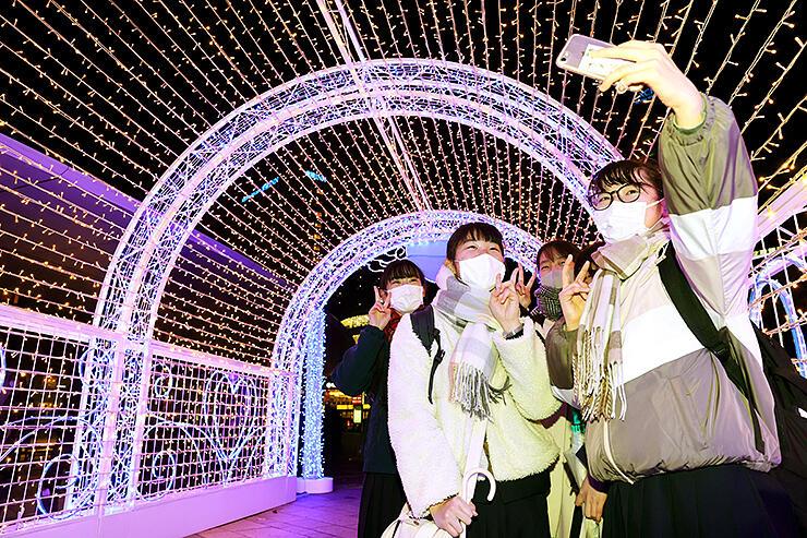 イルミネーションゲートの中で記念写真を撮る高校生=富山駅南口前広場
