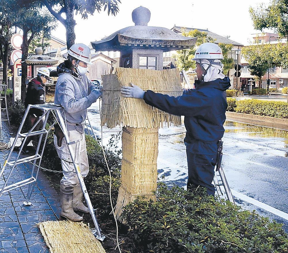 石燈籠にこもを掛ける職人=加賀市山代温泉