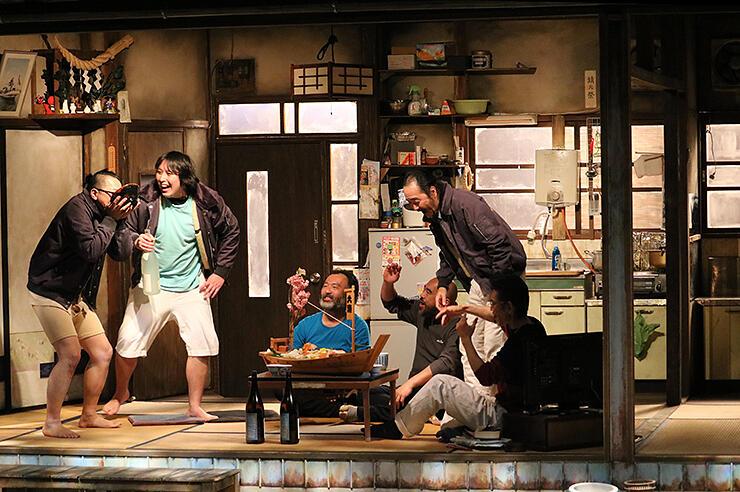 リアルな四軒長屋のセットで、漁師を演じる出演者たち