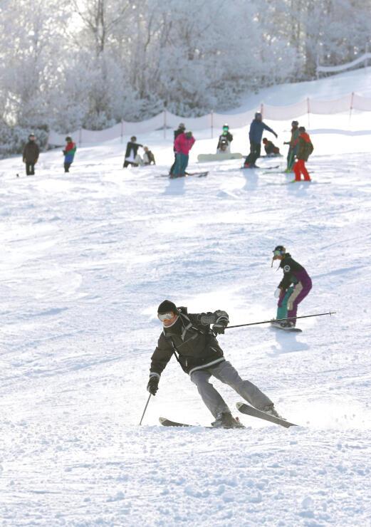 県内で最初にオープンしたかぐらスキー場で、スキーなどを楽しむ人たち=2日、湯沢町三俣