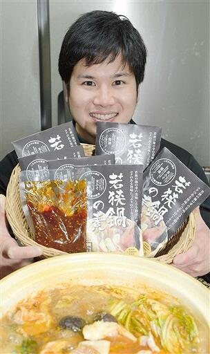 開発した「若狭鍋の素」を手にPRする男性=12月2日、福井県おおい町名田庄三重のスーパー「カネイチ」