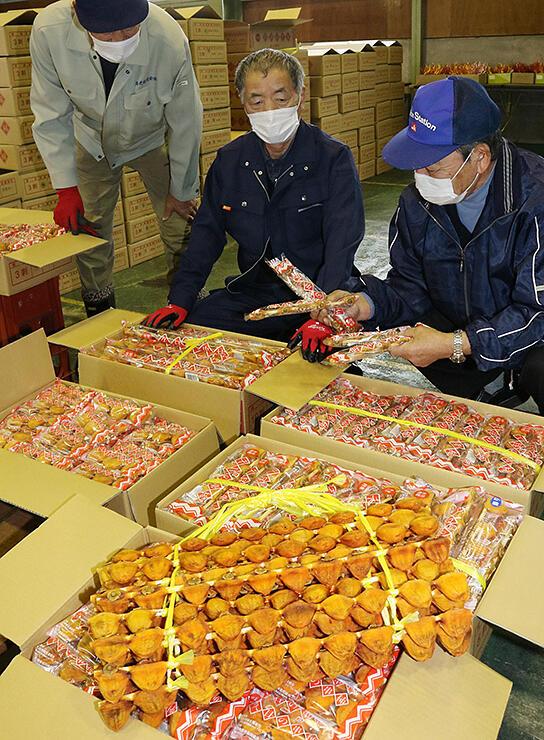 上々の仕上がりとなった串柿を確認する宝住組合長(中央)ら