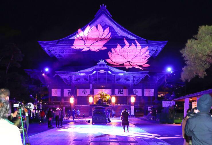 試験点灯でハスの花などが投影された善光寺本堂=3日午後5時46分