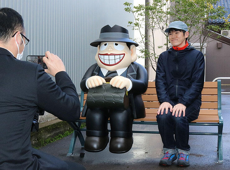 「喪黒福造のスマイルベンチ」で記念撮影するファン=氷見市本町