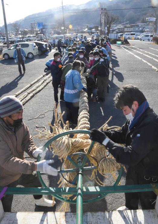 専用の器具を使い、力を合わせてしめ縄を作る地元の氏子たち=6日午前9時10分、諏訪市