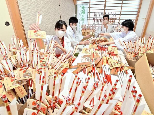 破魔矢に絵馬を丁寧に取り付ける神職や巫女=12月7日、福井県敦賀市の気比神宮