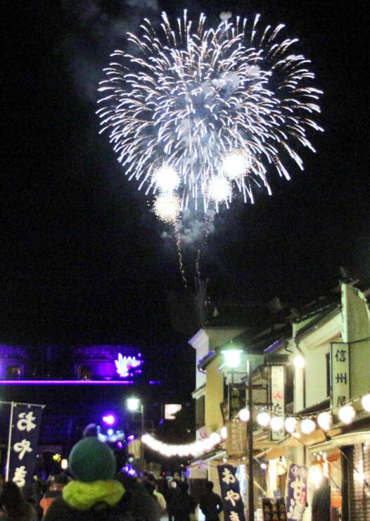 イルミネーションに合わせて打ち上げられた花火。仲見世通りからはライトアップされた山門(左奥)越しに見えた=6日午後7時3分