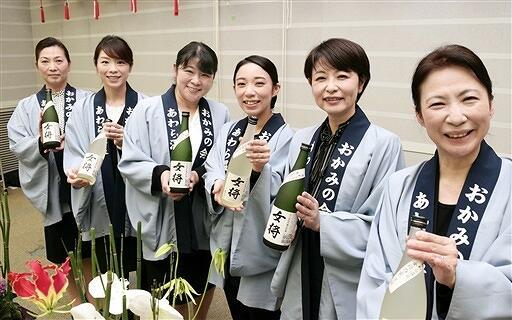 今年の純米吟醸酒「女将」を手にするあわら温泉女将の会のメンバー=12月8日、福井県あわら市の芦原温泉旅館組合