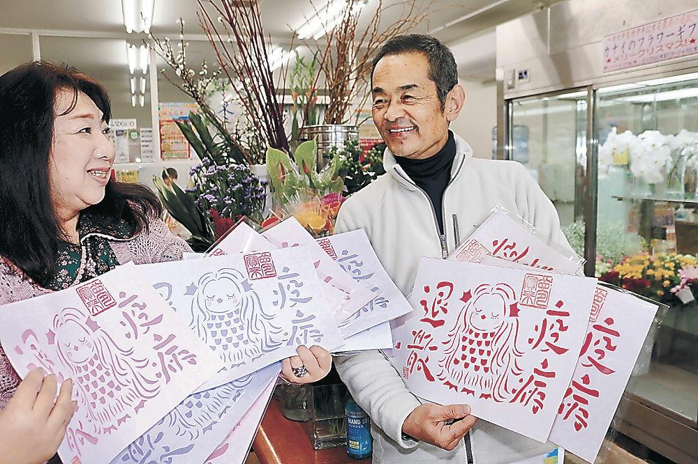 「アマビエ」の切り絵を贈る辻口さん(左)=羽咋市内の花き店
