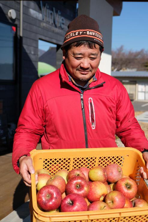 1コンテナ分のリンゴを持ってプロジェクトをPRする竹村さん