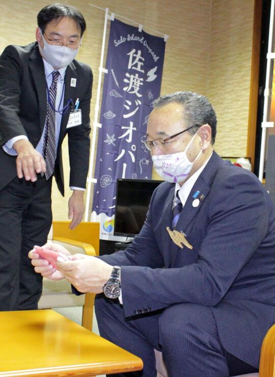 ゲームを体験する渡辺竜五市長=9日、佐渡市役所