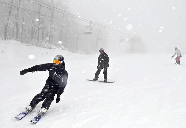 雪が降る中、初滑りを楽しむスキーヤーやボーダーたち=12月18日、福井県勝山市のスキージャム勝山