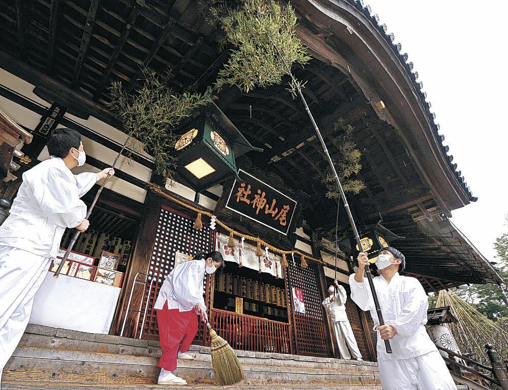 クロダケで拝殿を清める神職=尾山神社