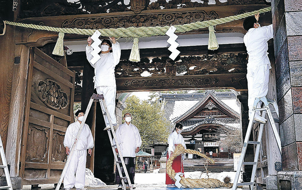 真新しいしめ縄を取り付ける神職=尾山神社