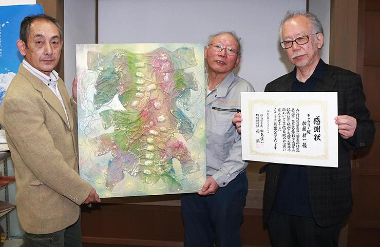 寄贈された「概念」や感謝状を手にする(左から)中島さん、西さん、加藤さん