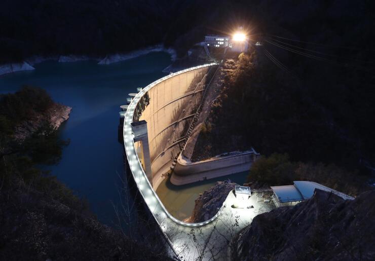 ライトアップして渓谷に浮かび上がった小渋ダム=24日午後5時5分、中川村