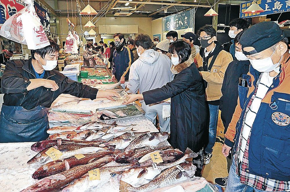 正月用の食材を品定めする来場者=無量寺町のいきいき魚市