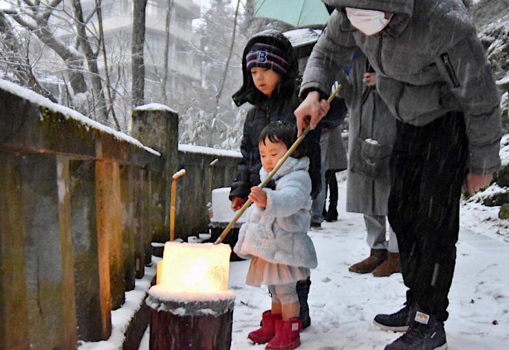 氷の灯籠に火をともす家族連れ