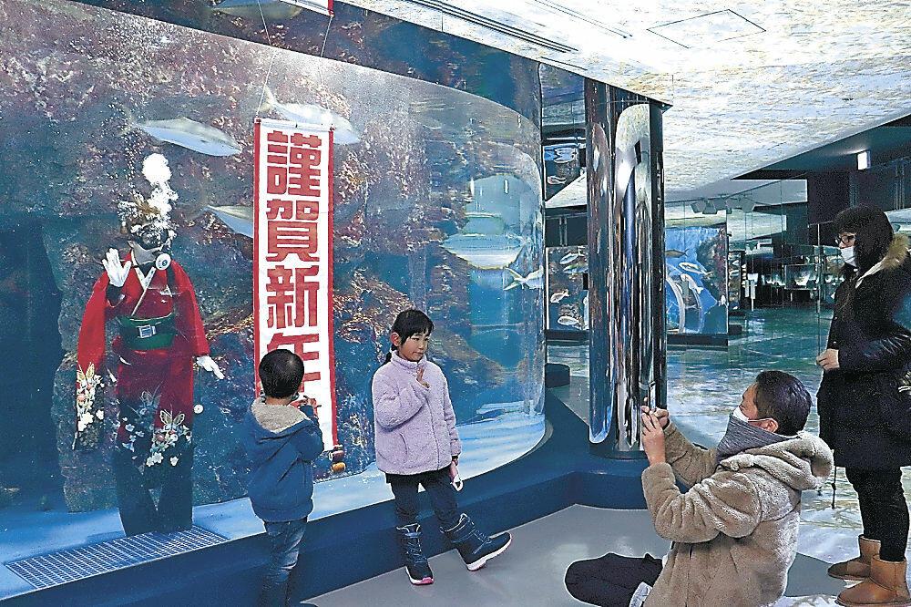 晴れ着のダイバーと記念撮影をする来場者=七尾市ののとじま臨海公園水族館