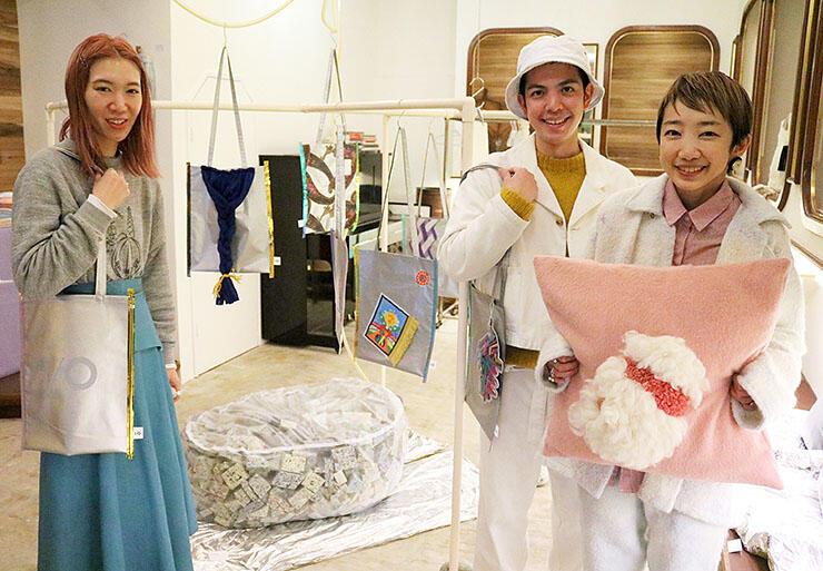 斬新なデザインのトートバッグやクッションなどを紹介する荻野さん夫婦(右)とオーナーの花本さん(左)