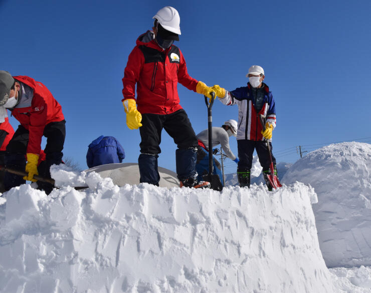 スコップで形を整えながら、雪を踏み固める隊員ら=7日