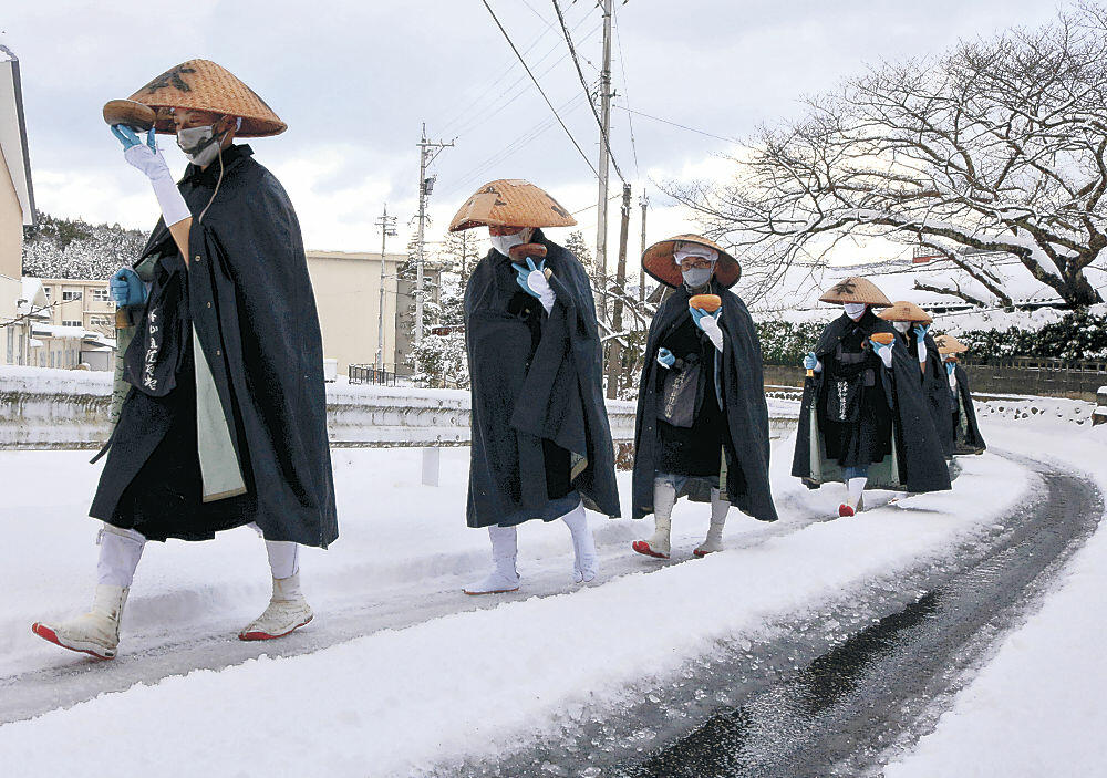 雪の中、町内を巡る僧侶=輪島市門前町