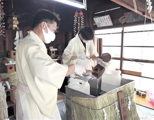 火災を防ぐとされる「火伏せの水」を参拝者に配る神事=1月12日、福井県越前市武生柳町の末広神社