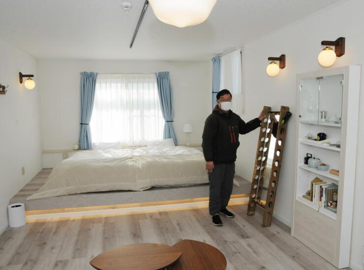 開業した宿泊施設の客室を紹介する小山社長。窓からワイン用ブドウ畑を一望できる