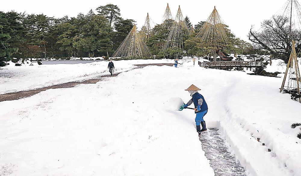 除雪して通路を作る作業員=兼六園