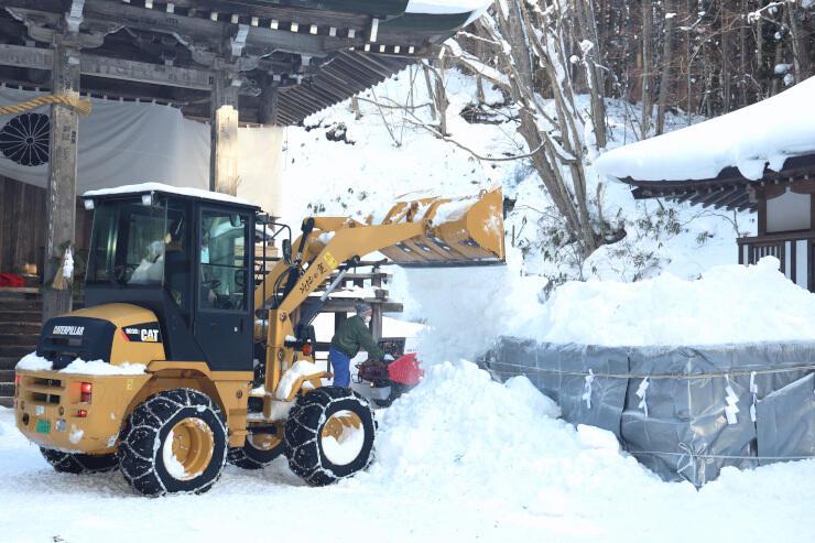重機を使って酒瓶を雪で埋める関係者たち