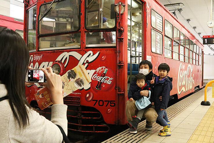 「コカ・コーラ レトロ電車」をバックに記念撮影する家族連れ=万葉線高岡駅