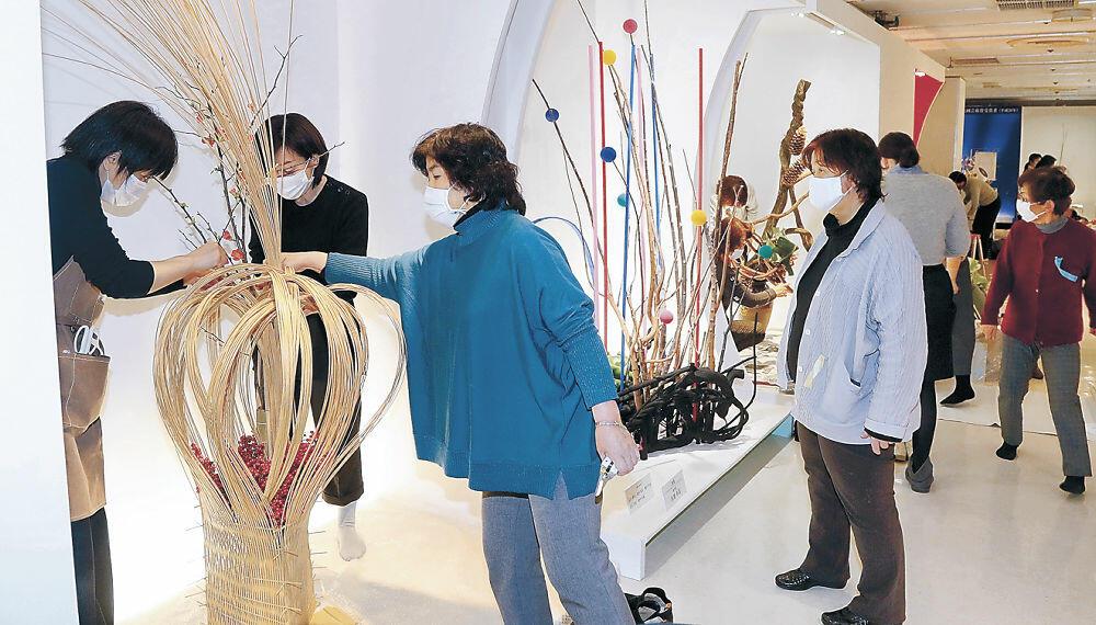 勢いのある大胆な花材使いで制作を進める出品者=金沢市のめいてつ・エムザ8階催事場