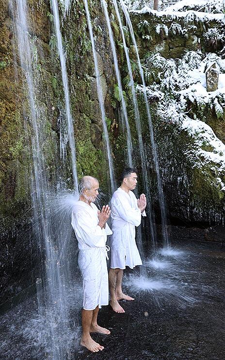 滝に打たれて寒修行に励む男性たち=大岩山日石寺