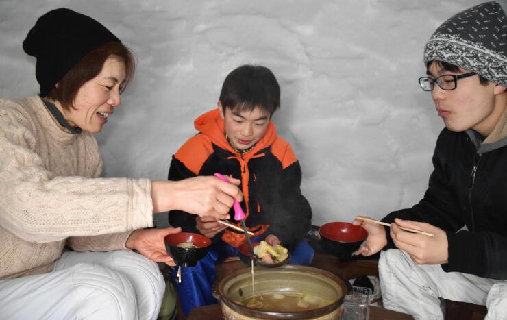 かまくらの中で「のろし鍋」を味わう田辺さん親子