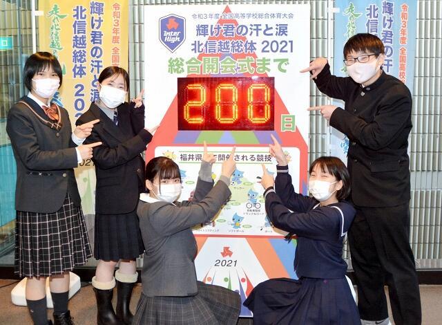インターハイの総合開会式まで200日となり、カウントダウンボードを指さす活動推進委員の高校生たち=1月25日、福井県庁
