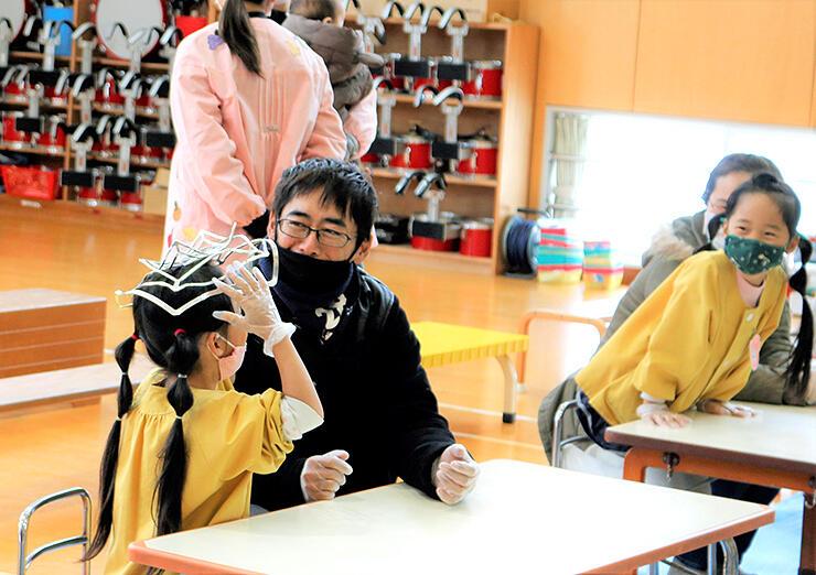 野村保育園で行われたワークショップでスズ製の曲がる器に触れる親子