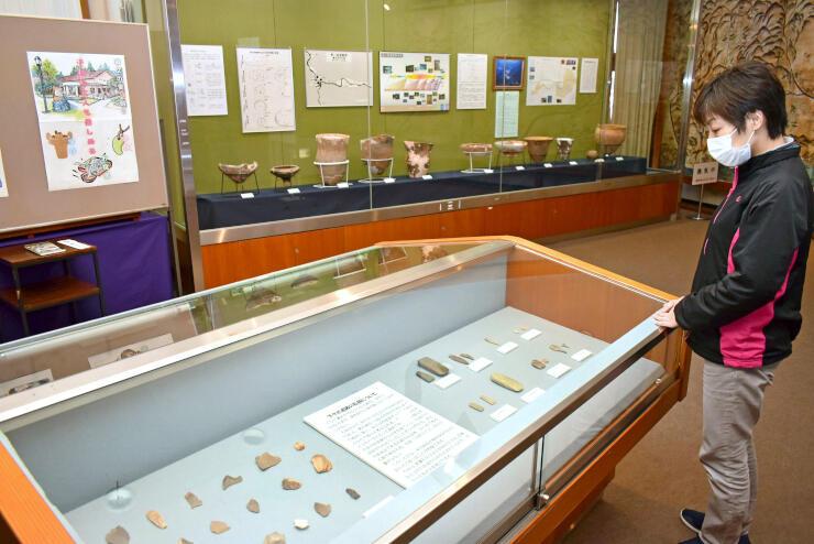 下クボ遺跡から出土したさまざまな形状の土器などが並ぶ会場=村上市三之町