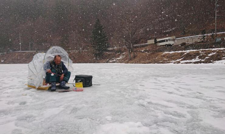 雪の降る中、立岩湖で穴釣りをする男性