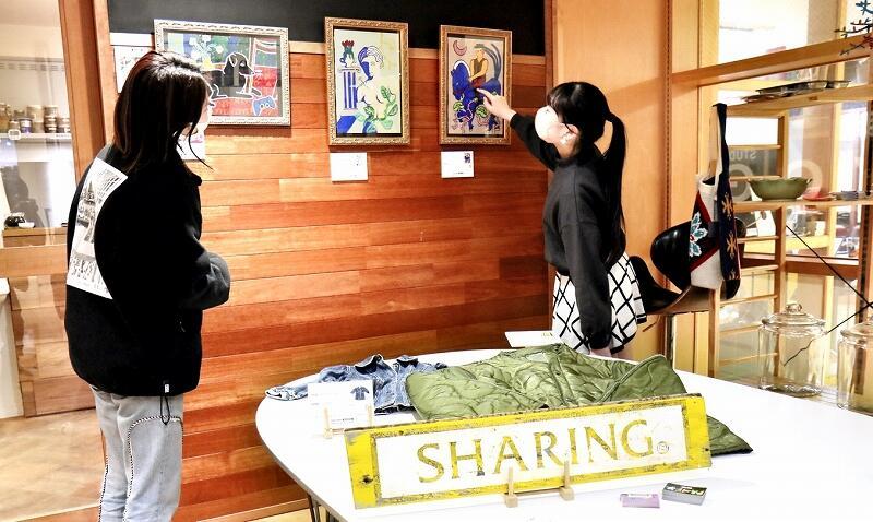 福井市中心市街地のカフェで展示されたアーティストの直筆絵画や私服=1月29日、同市中央1丁目の「Livin' for green」
