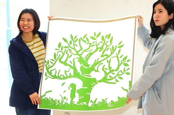 メインホールの壁面を彩るデザインの原案に採用された眞崎さん(左)の作品