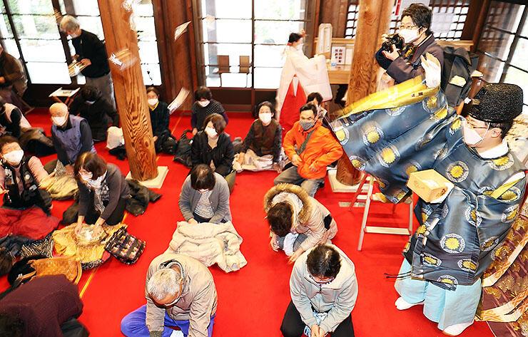 間隔を空けて座る参拝者に袋入りの豆をまく神職=高瀬神社