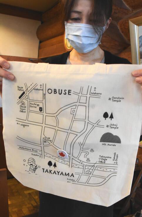 須高地域の地図がデザインされたトートバッグ。缶バッジを留めていく