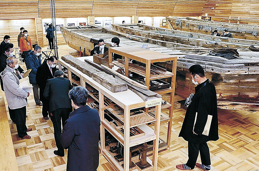 展示品を見て回る完成式の出席者=能登町真脇の「能登内浦のドブネ収蔵庫」