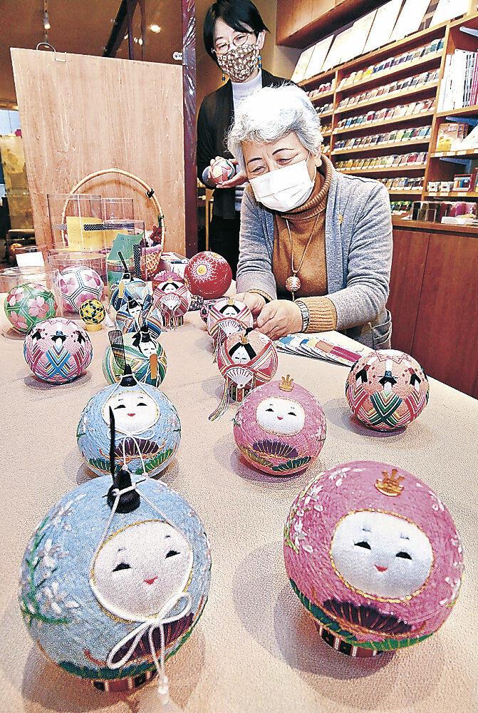加賀てまりや加賀八幡起上りをイメージしたひな飾りを並べる小出さん(手前)=南町