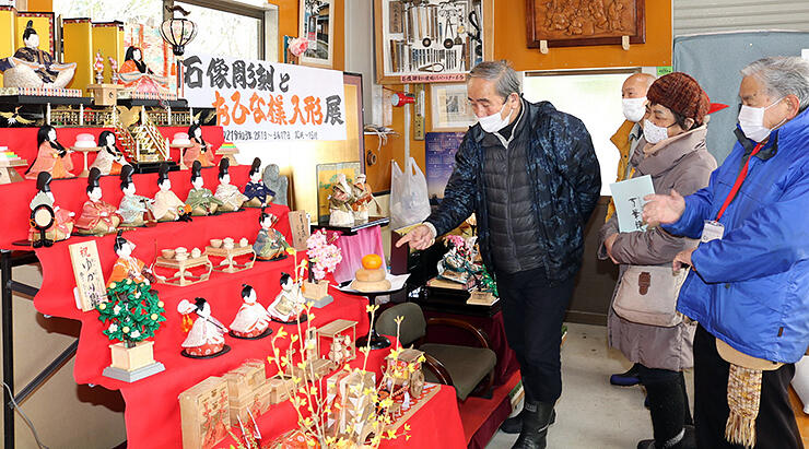 ひな人形を見る松村さん(右)と来館者